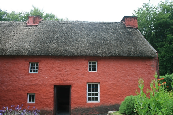 Thatched house with stone walls painted red