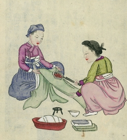 Two people using pan iron on length of fabric