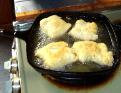 frying bannocks in frypan on top of stove