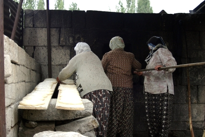 women baking flatbread at cement block oven