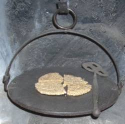 Quartered oat cake on metal gridiron with spade