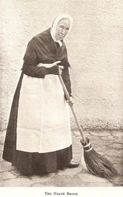 Elderly English woman in white pinafore holding broom