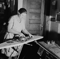 Woman using sad iron on folding ironing board