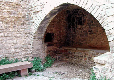 Open stone arch leads to roofed baking space