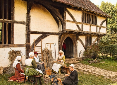 Tudor costumed women doing basketwork outside timber frame house